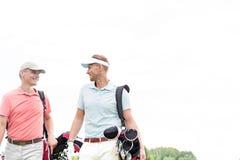 Golfistas de sexo masculino felices que comunican contra el cielo claro imagen de archivo