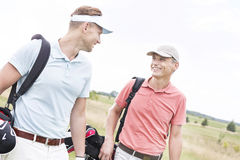 Golfistas de sexo masculino felices que conversan contra el cielo claro Imagen de archivo