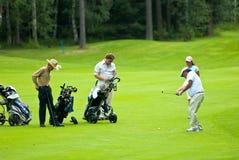 Golfistas del grupo en feeld del golf Imagen de archivo libre de regalías