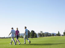 Golfistas que caminan en campo de golf Imagen de archivo