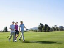Golfistas que caminan en campo de golf Fotografía de archivo libre de regalías