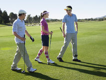 Golfistas que caminan en campo de golf Fotos de archivo