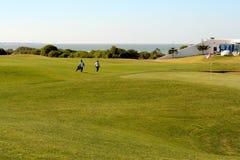 Golfistas que recorren en el campo de golf Fotografía de archivo libre de regalías