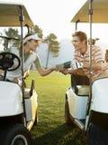 Golfistas que se sientan en los carros de golf que sostienen la tarjeta de la cuenta foto de archivo