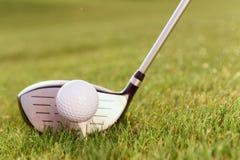 Golfklubb och boll på utslagsplats Arkivfoto