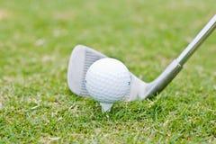 Golfklubb och golfboll på gräs Royaltyfri Foto