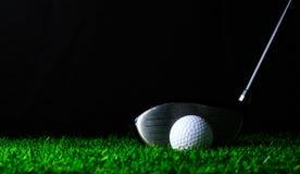 Golfklubb och golfboll på grönt gräs arkivbilder