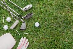Golfklubbar, golfbollar, golfhandske och lock på gräs arkivbilder