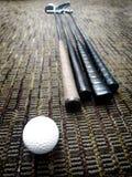 Golfklubbar och boll i regeringsställning på matta Royaltyfri Foto
