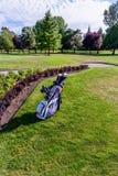 Golfklubbar och golfvagn på gräset i en golfklubb royaltyfri bild