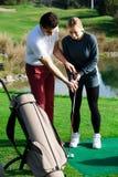 Golflagledaren förklarar grunderna av en golfare som slår bollen Royaltyfri Bild