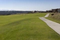 Golflandgoed met huizen en weg Stock Fotografie