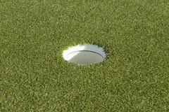 Golfloch auf einem Feld Stockbild
