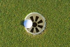Golfloch auf einem Feld und einem Golfball Stockfoto