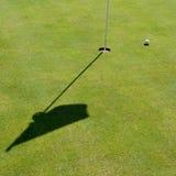 Golfloch, -markierungsfahne und -kugel Stockfotos