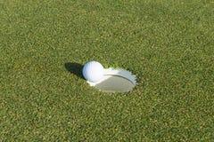 Golfloch und -ball auf einem Feld Lizenzfreies Stockfoto
