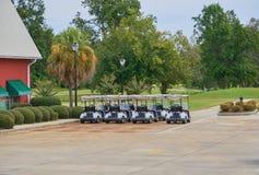 Golfmobile parkten in den Reihen nahe den Klubhauswartegolfspielern Lizenzfreies Stockbild