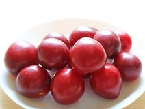 Golfo maduro Ruby Plum Fruits Piled del color rojo para arriba en la placa blanca Fotos de archivo libres de regalías