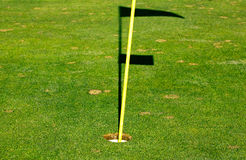 Golfowa dziura na zieleni z dziura zapasem i cieniem flaga Fotografia Stock