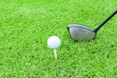 Golfowego trójnika piłki klubu kierowca w zielonej trawy kursowym narządzaniu sho Fotografia Stock
