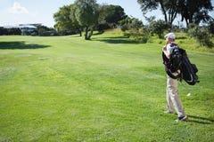 Golfowy gracz niesie jego odprowadzenie i torbę Zdjęcie Royalty Free