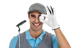 Golfowy gracz pokazuje piłkę golfową i trzyma kija golfowego fotografia stock