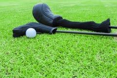 Golfpåsar och golfboll på en utslagsplats i grönt gräs jagar royaltyfri fotografi