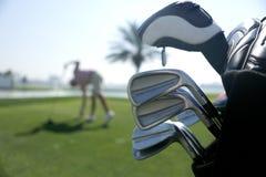 Golfpåse med klubbor på planet och med spelaren för gunga i bakgrunden arkivfoton