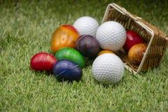 Golfpåsk med golfboll och påskägg på grönt gräs arkivbilder