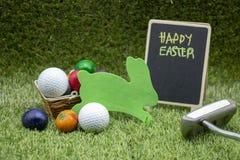 Golfpåsk med golfboll och påskägg på grönt gräs royaltyfri bild