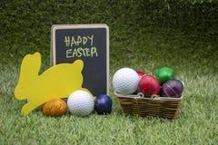 Golfpåsk med golfboll och påskägg på grönt gräs arkivbild
