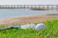 Golfpinne och boll på gräs med en bakgrund av naturen. Arkivbilder