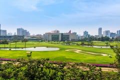 Golfplatz im Hirsch von Bangkok, Stadtskyline im Hintergrund lizenzfreie stockfotografie