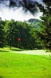Golfplatz mit roter Fahne in der Mitte Lizenzfreie Stockbilder