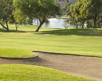 Golfplatz mit sandtrap und See Stockfotos