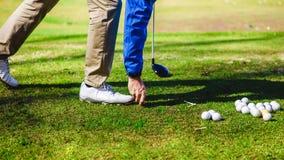 Golfplayer e uma bola Imagens de Stock