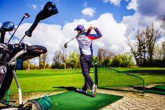 Golfplayer hits a ball. On the grass stock image