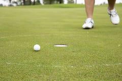 Golfplayer walking to hole Royalty Free Stock Photo