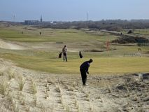 Golfplayers on a golf court in The Netherlands. Two golfplayers on a golfcourt in the dunes of Holland Stock Image