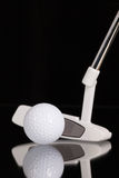 Golfputter- och guldutrustningar på den svarta glass tabellen Arkivfoto