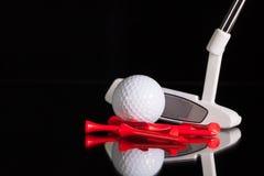 Golfputter- och guldutrustningar på det svarta glass skrivbordet Fotografering för Bildbyråer