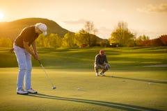Golfspelare för två pensionär på solnedgången Royaltyfria Bilder