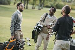 Golfspelare med golfklubbar som har gyckel på golfbana Royaltyfria Foton