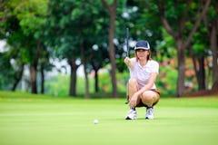 Golfspelare med putter Arkivbild