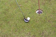 Golfspelare på den sättande gräsplanen som slår bollen in i ett hål Royaltyfri Fotografi