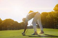 Golfspelare som förlägger bollen på utslagsplats fotografering för bildbyråer