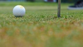 Golfspelare som sätter bollen in i hålet, endast fot och järn som ska ses Arkivfoto
