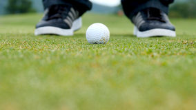 Golfspelare som sätter bollen in i hålet, endast fot och järn som ska ses Arkivbild