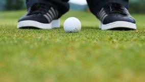 Golfspelare som sätter bollen in i hålet, endast fot och järn som ska ses Royaltyfria Foton