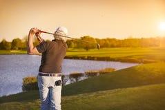 Golfspelare som teeing-av på solnedgången Royaltyfri Foto